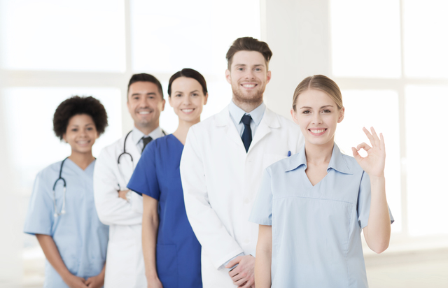 international, profession, people and medicine concept - group of happy doctors and nurses at hospital showing ok hand sign